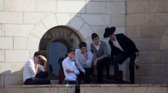 Ultra-Orthodox Jews watch the scene outside the synagogue where at least 4 people were killed by terrorists.