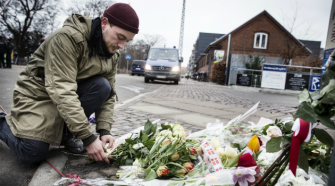 Nation in Mourning: Danish man lays flowers outside the main synagogue in Copenhagen where a guard was shot and killed.