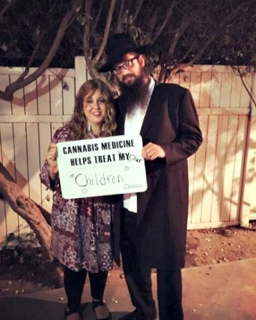 Shifra Klein poses with her husband, with a sign showcasing their support medical marijuana.