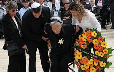 A Holocaust survivor gets help laying a wreath at a Yom HaShoah ceremony at Yad Vashem, May 2, 2011.