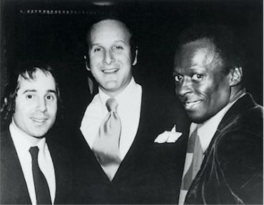 Recording legend Clive Davis (middle) stands with Paul Simon (left) and Miles Davis.