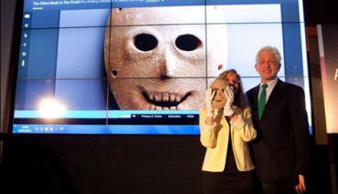 Israel Museumdirector James Snyder and curator Debby Hershman holding a Neolithic stone mask with the Google Art Project projected in the background, April 3, 2012.