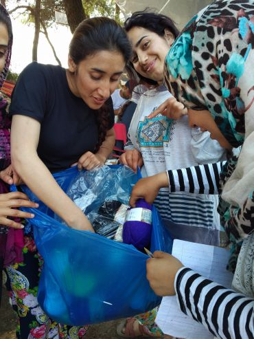 Yazidi girls get knitting supplies provided by the author.