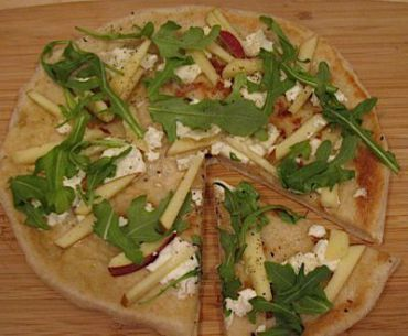 A Rosh Hashana pizza is covered with apples and honey, dotted with chevre and sprinkled with arugula and pine nuts
