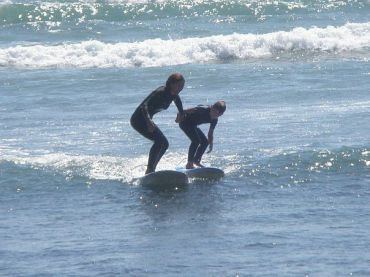Navah Paskowitz-Walther surfs with one of her sons.