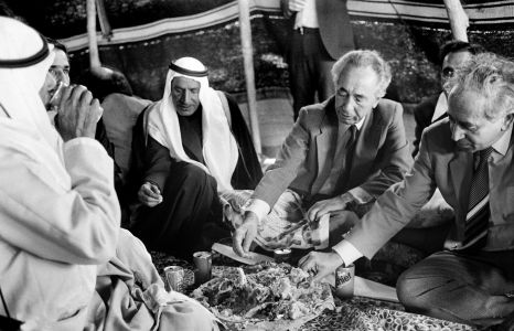 January, 1985:  Shimon Peres enjoys a bedouin style meal under a traditional nomad's tent in the Negev desert.