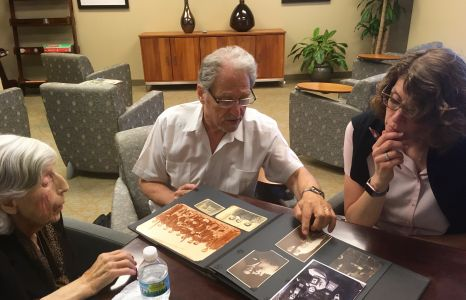 Brenda and Fred Huss and Susan Snyder look over the Huss family photo album