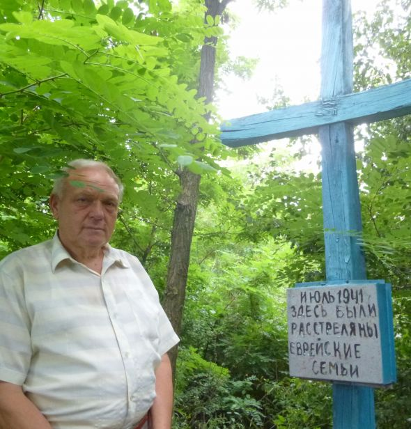 Village school principal Ivan Timoshko stands next to the memorial he and his students built for the Jews massacred there during World War II.