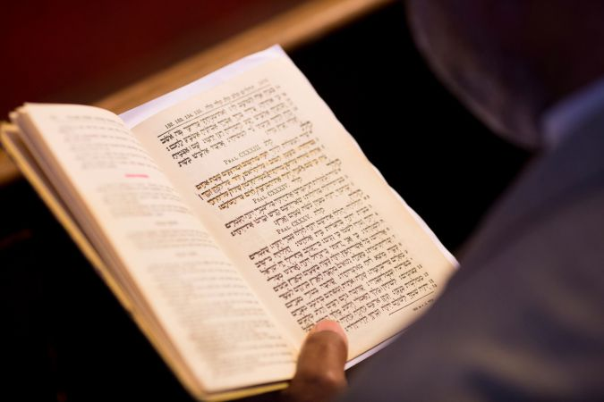 Davening: A worshipper at B'nai Adath Kol Beth Yisrael follows the service in his Hebrew-English language psalm book.