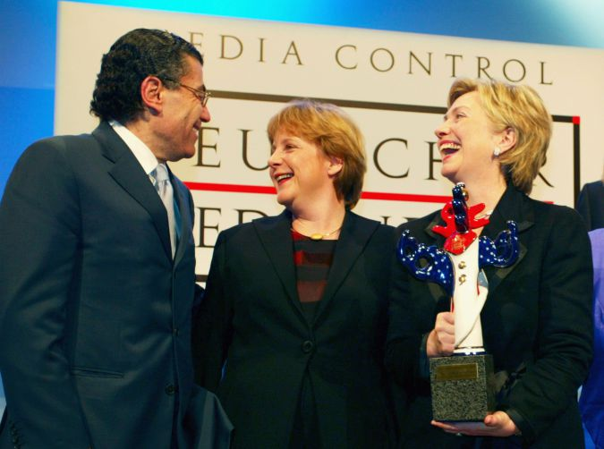 Hollywood mogul Haim Saban (L) is a self-described one-issue man and that issue is Israel, on which he advises Hillary Clinton (R). In the middle is Angela Merkel.