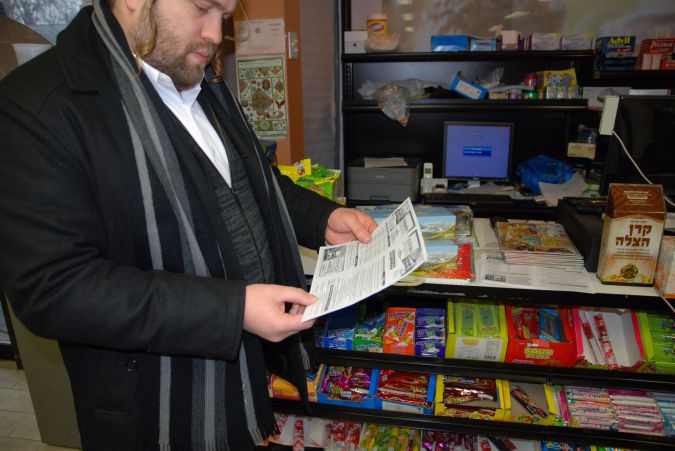 At the kosher grocery store in Bloomingburg, a Hasidic resident shows off the new Yiddish community newsletter.