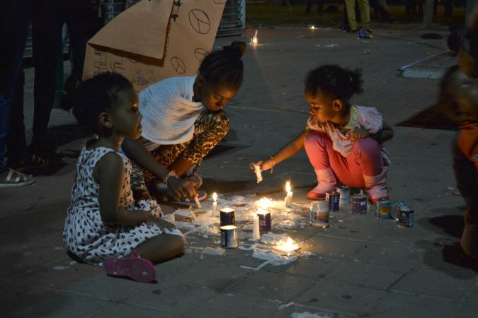 Children light candles at memorial for Eritrean immigrant killed by mistake after a terror attack in the town of Beersheba.