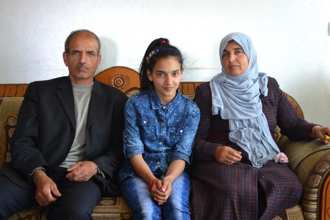 Dima Al Wawi, believed to be the youngest female Palestinian prisoner, sits between her parents Ismail Al Wawi and Sabha Al Wawi.