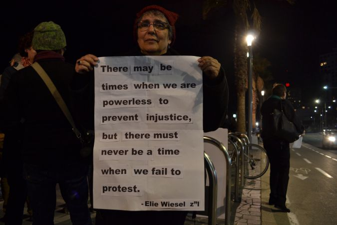 Chana Tyman-Levy holds a sign with a quote from Elie Wiesel.