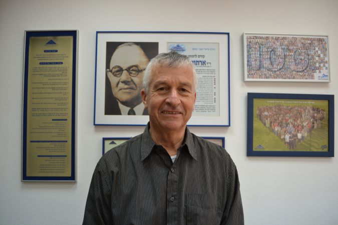 Yosi Ben Dov, the principal of the Reali school, in front of a photo of the school founder Arthur Biram.