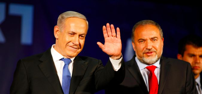 Benjamin Netanyahu waves to supporters with Avigdor Liberman at his election campaign headquarters on Janurary 23, 2013 in Tel Aviv, Israel.
