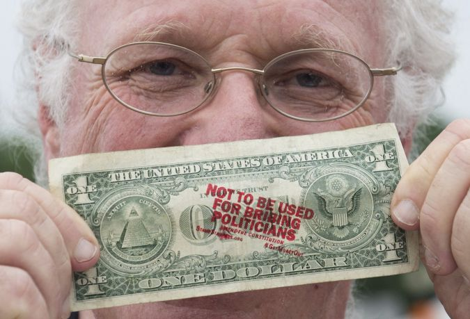 Ben Cohen, co-founder of Ben & Jerry's Ice Cream, holds up a one-dollar bill he stamped with the words 'Not to be used for bribing politicians' as he advocates to get money out of politics, outside Union Station in Washington on June 18, 2013.