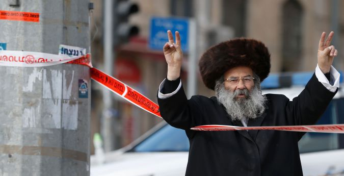 An ultra-Orthodox Jewish man gestures the v-sign for victory from behind police tape at the site of a reported attack by a Palestinian assailant on December 26, 2015, near Jerusalem's Old City. 'Police officers spotted a man who aroused their suspicions and approached him to check,' a police spokeswoman said. 'The terrorist pulled out a knife and tried to stab the policeman and was quickly killed by police gunfire.