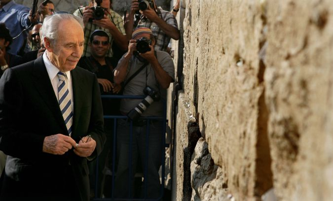 June, 2007: Peres places a note at the Western Wall after being elected president of Israel.