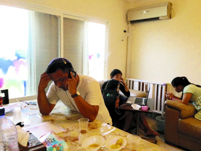 Modern Family: Hanoch Haokip,  talks on his cell phone at home in Akko while his daughters immerse themselves in screens.
