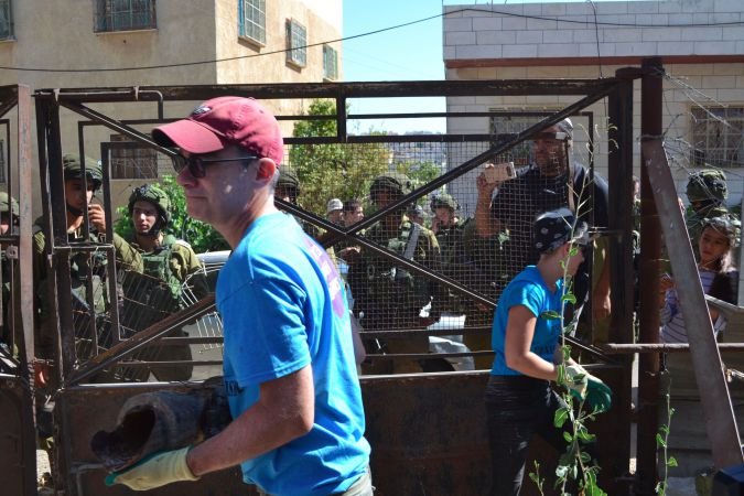 Brant Rosen, a Chicago rabbi, helps clear a yard as an activist project in Hebron, as soldiers and settlers watch.