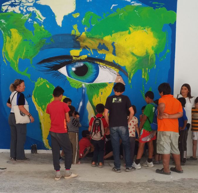 A children's activity under against a mural created by the refugees.
