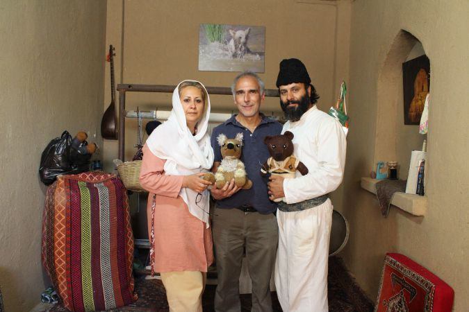 Larry Cohler Esses with Aghamir Miri and his wife, holding replicas of the bears they want to protect.