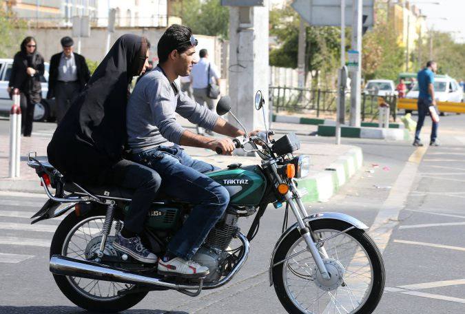 Iranian youths ride a motorcycle to bypass chronic traffic in central Tehran.