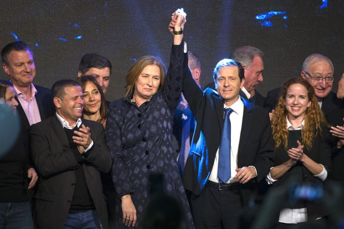 Tzipi Livni of Hatnua and Yitzhak Herzog of Labor clasp hands at a 2015 campaign event for their Zionist Union party, with Stav Shaffir at right.