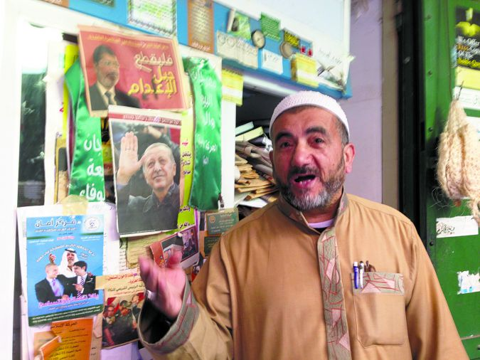 Season's Greetings: Shiekh Muhammad Abu Anas, the imam at a Nazareth mosque, in front of his shop, decorated with photos of Islamist leaders.