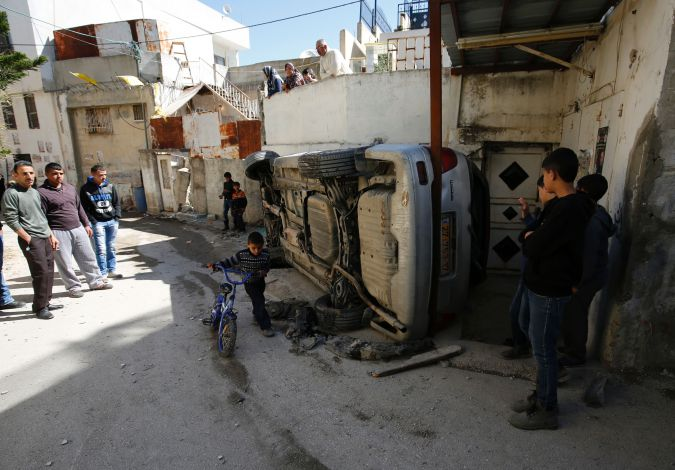 Palestinians examine wreckage of vehicle after firefight with Israeli troops in West Bank refugee camp.