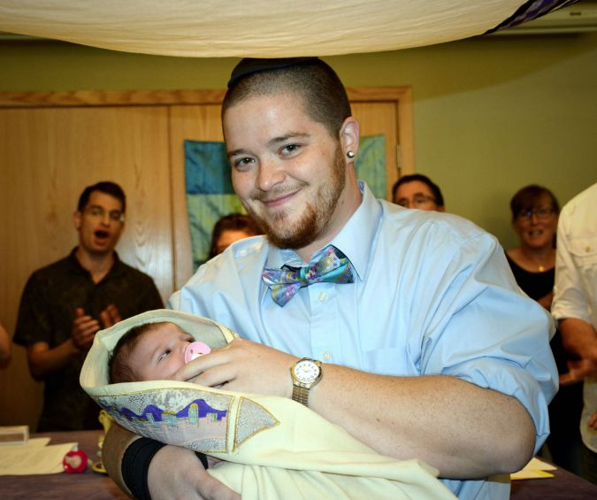 Rafi holds his daughter, Ettie, at her simchat bat Jewish welcoming ceremony in October.