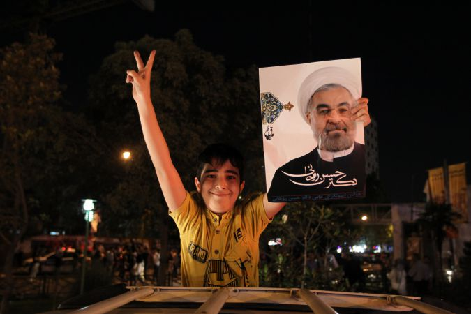 Celebration: Supporters of Iranian then-presidential candidate Hassan Rouhani hold portraits of him at street rally in 2013.