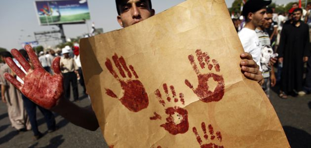 Tumult: A supporter of the Muslim Brotherhood and ousted Egyptian president Mohamed Morsi shows his blood-stained hand while holding a placard bearing handprints made with the blood of victims who were shot during a gun battle outside the Cairo headquarters of the Republican Guard on July 5.