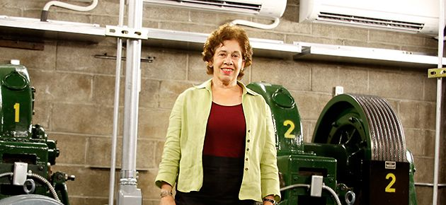 Rising: AJC?s Linda Lansky stands next to new, energy-efficient elevator equipment.