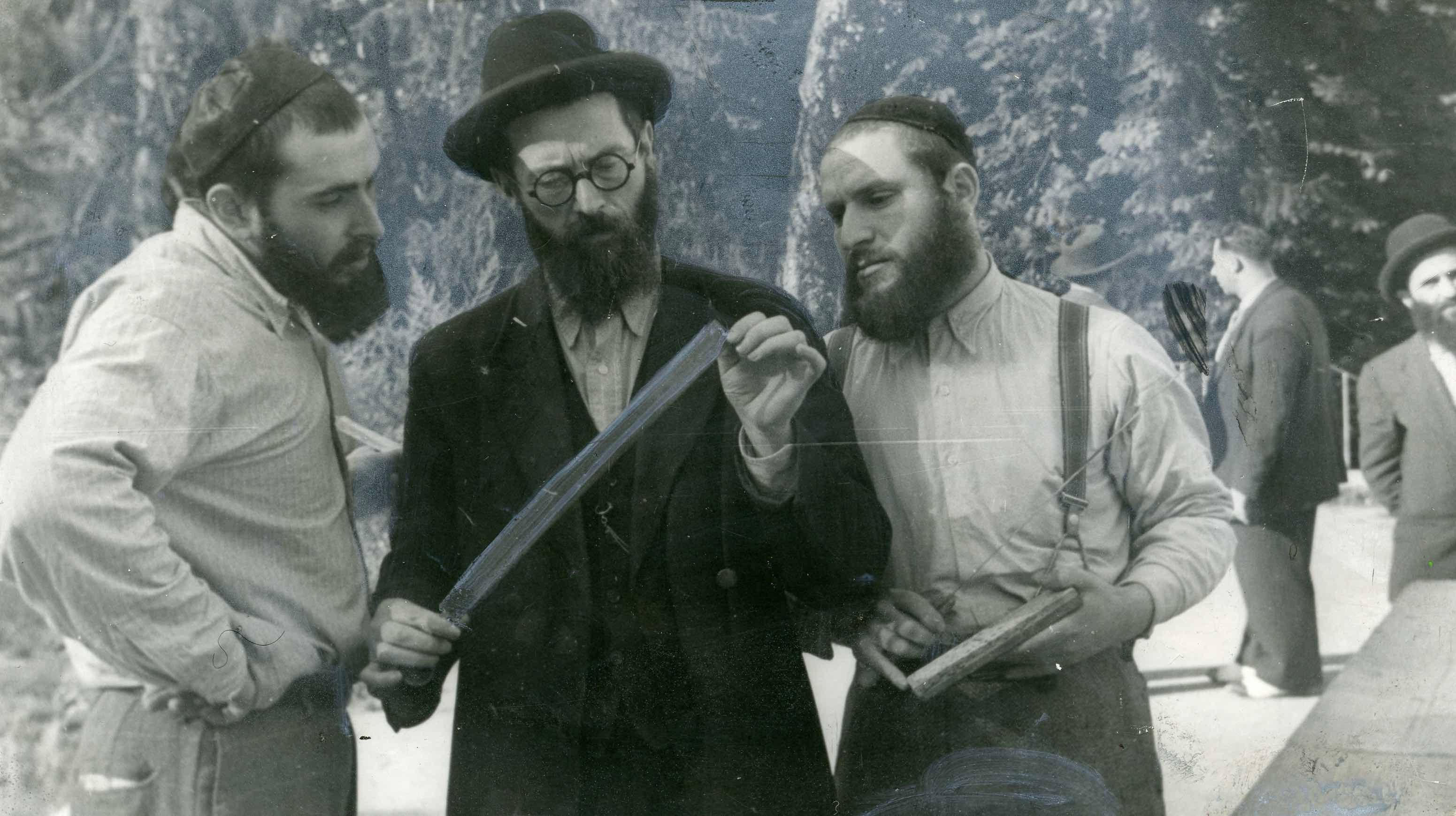 In 1948, the mahgiekh (kashrut supervisor)Reb Berl Yankl looks over the sharp slaughter knife to ascertain that it has no flaw.