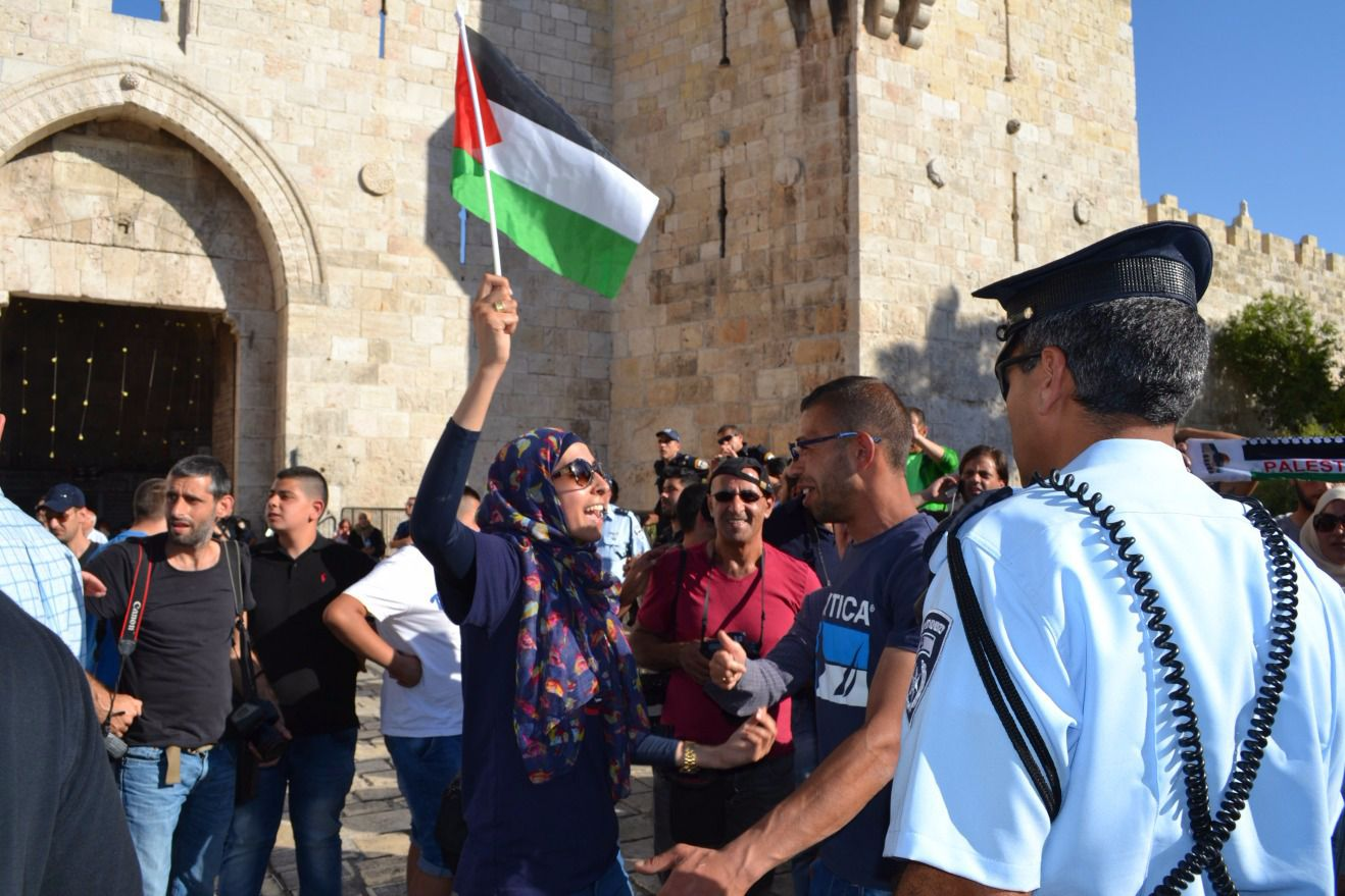 Palestinian woman waves flag as Jewish marchers celebrate Jerusalem Day in the city's Arab quarter.