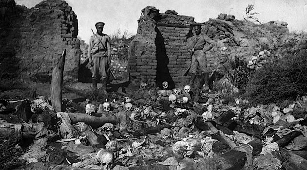 Aftermath of Genocide: In 1915, soldiers stand over skulls of victims from the Armenian village of Sheyxalan in the Mush valley.