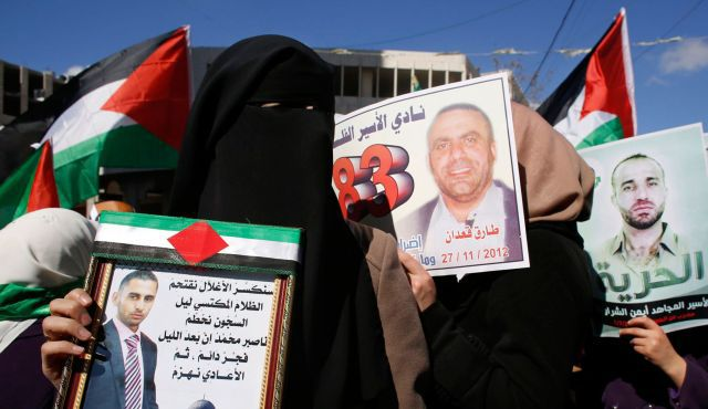 A Palestinian woman holds a photograph of a prisoner on hunger strike during a rally in the West Bank city of Hebron to show solidarity with prisoners on hunger strike in Israeli jails, in February.