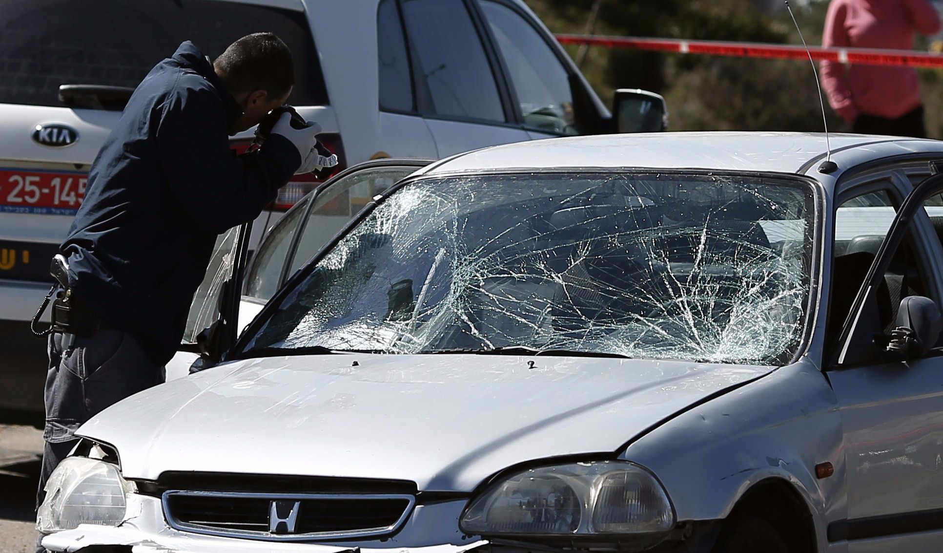 Israeli forensic police inspect a car that ploughed into pedestrians in Jerusalem injuring several people during a similar attack in March 2015.