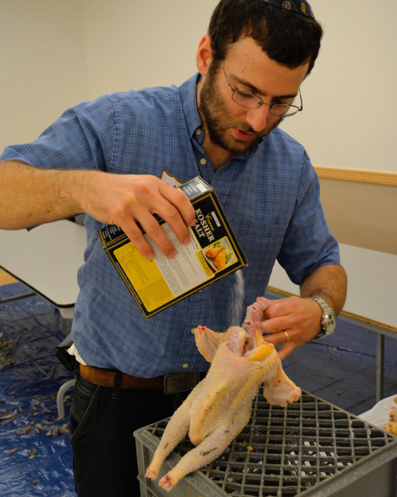 After draining the chicken of blood, Grow and Behold founder and owner Naftali Hanau removes the rest of the blood by coating it in kosher salt.