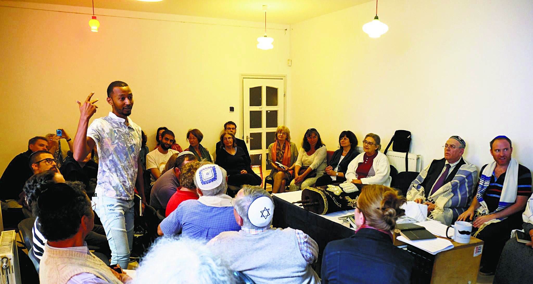 Welcoming the Stranger: Mussa Kilam, an Eritrean immigrant, tells his story to listeners at a 'Jewish Solidarity with Refugees' event at Auróra, a popular Budapest gathering place for young Jews, on October 1.