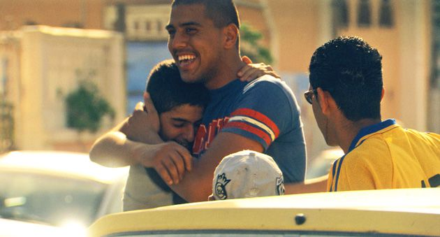 Brotherly Love: Omar (Shahir Kabaha) gets a hug from his little brother Nasri (Fouad Habash) on the streets of Ajami.