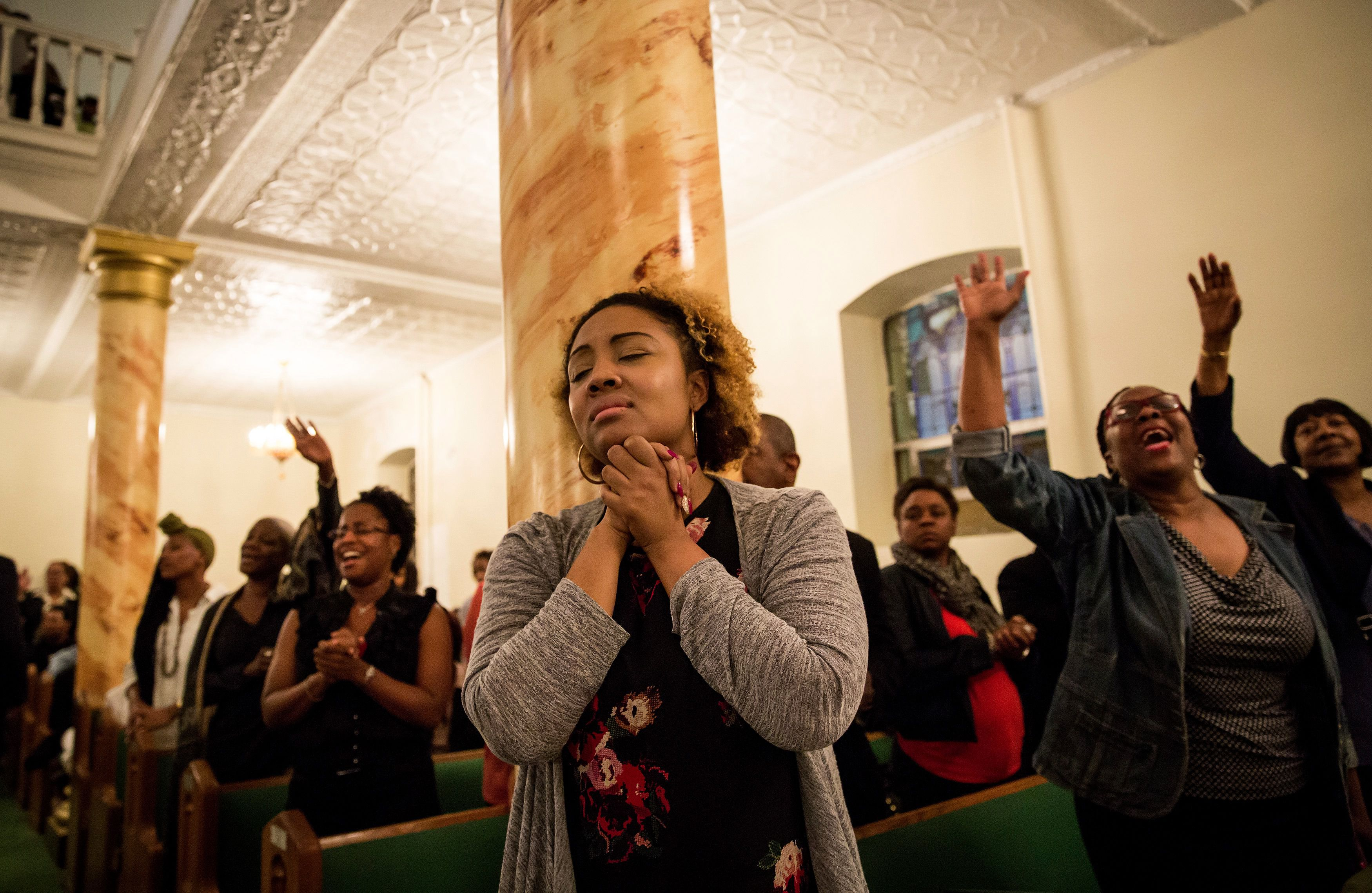 Open Arms: Mourners at the First African Methodist Episcopal Church Bethel in Harlem hold a prayer vigil one day after the murder of nine worshippers at a black church in Charleston.