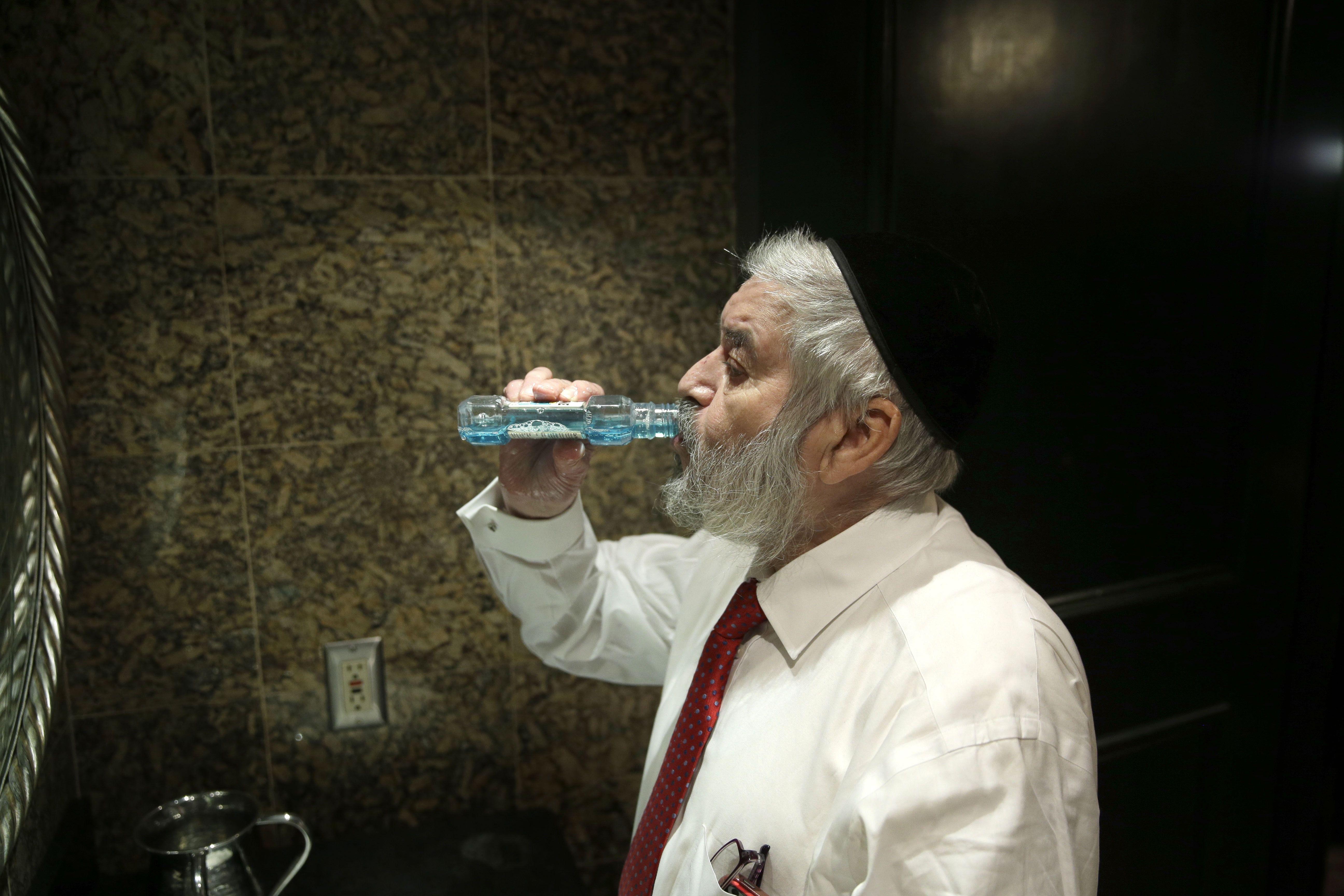Rabbi Avrohom Cohn rinses with mouthwash before performing metzitzah b'peh.