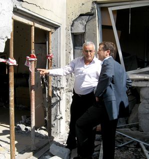 The Circle Widens: The mayor of Ashkelon, Roni Mahatzri, shows a member of Knesset one of the many scenes of destruction in his city after Hamas extended the range of rockets being launched from Gaza.