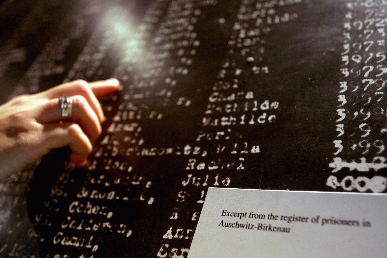A Yad Vashem visitor examines a list of Auschwitz-Birkenau prisoners.
