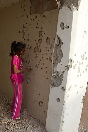 An Israeli girl surveys the damage from a rocket that hit a Beer Sheva school.