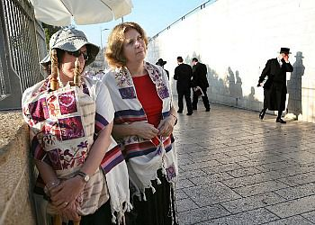 Anat Hoffman and another member of Women of the Wall stand at the entrance to the Kotel as Haredi men look away.