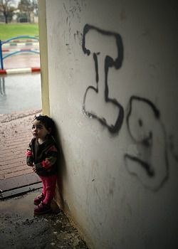 A two-year-old puts a bomb shelter to another use as she and her father take cover from rain on November 23, 2012 in Sderot, Israel.